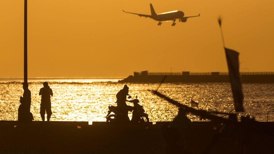 Ein Flugzeug fliegt über Bali bei Sonnenuntergang.