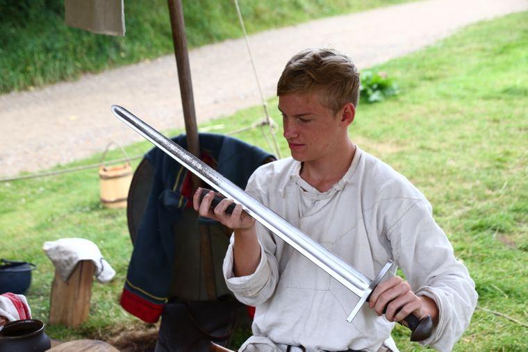 Thorben poliert sein Schwert im Ribe VikingeCenter.