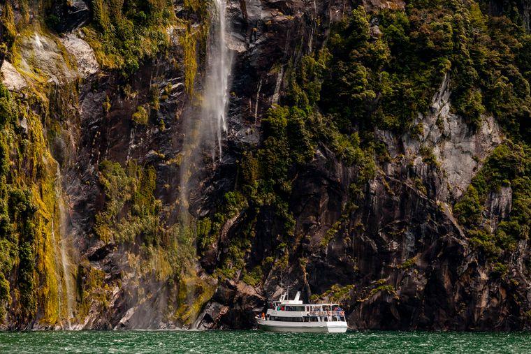 Bootstour unter Wasserfällen im Fiordland National Park in Neuseeland.