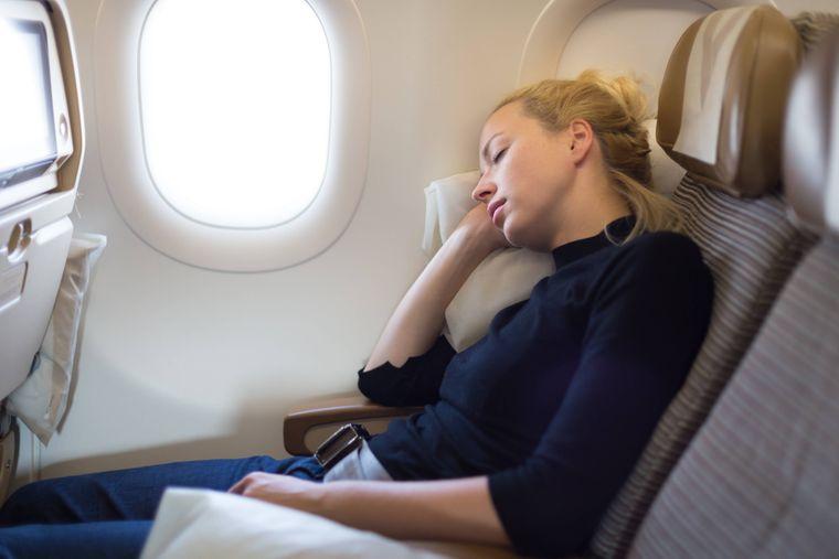 Eine Frau sitzt im Flugzeug am Fenster und schläft. Auch die Wahl des Sitzplatzes kann helfen, dass Betroffene stressfrei fliegen.