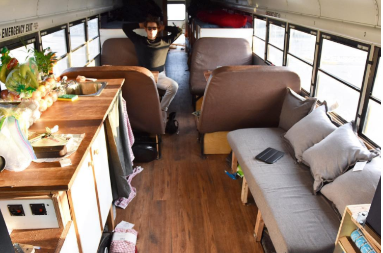 Ein junger Mann sitzt auf einem Sessel im alten Schulbus in Alaska.