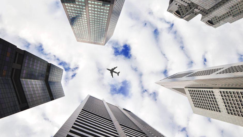 Flugzeug zwischen Wolkenkratzern.