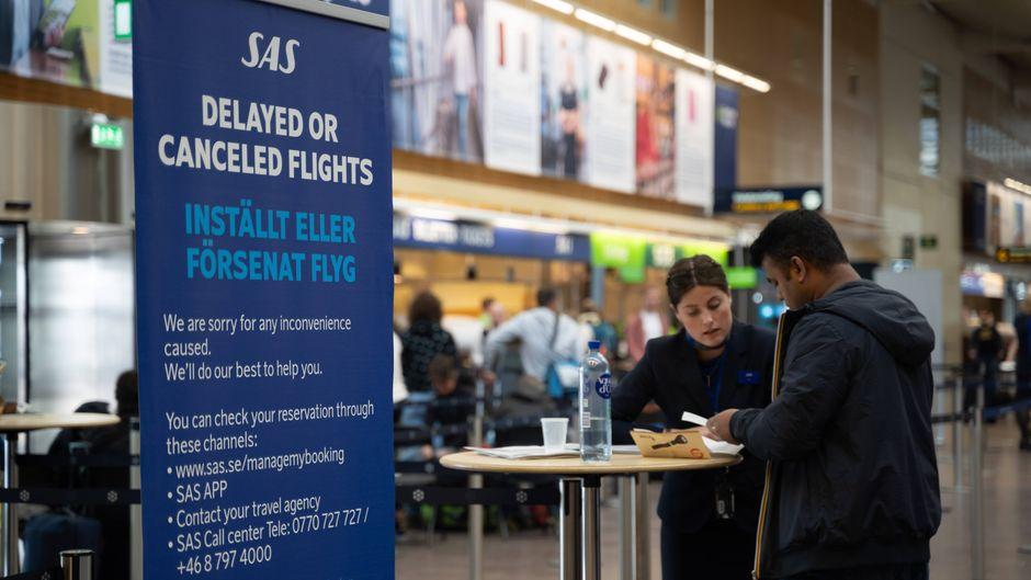 Passagiere lassen sich von SAS-Mitarbeitern am Flughafen in Stockholm beraten.