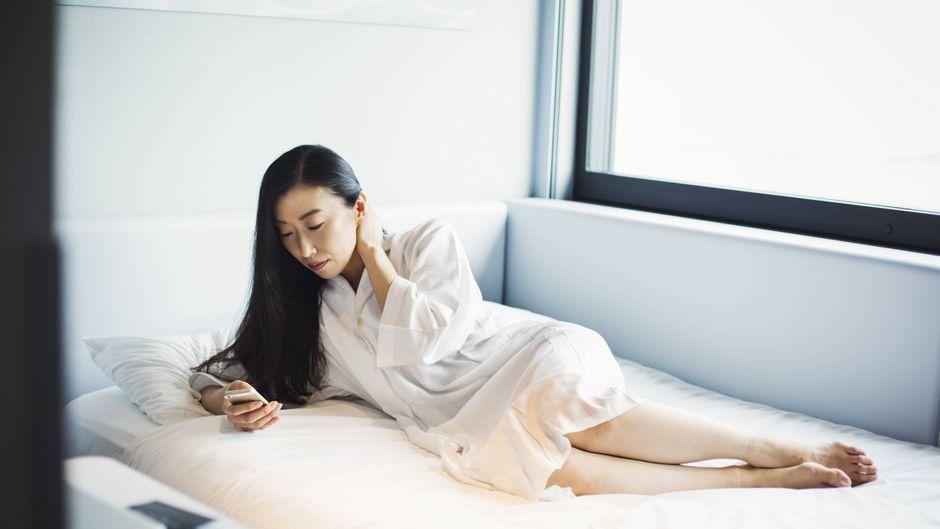 Eine Frau liegt nur im Bademantel im Bett und checkt ihr Smartphone.