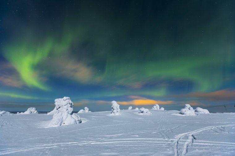 Polarlichter über einer ruhigen Winterlandschaft – das zu erleben steht auf der Bucket-List vieler Reisender.