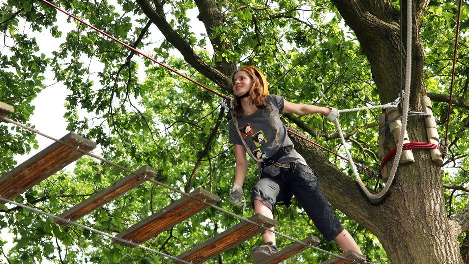 Ein junges, rothaariges Mädchen klettert im Hochseilgarten in Brandenburg. Gut gesichert mit einem Seil hangelt sie sich durch die Äste.
