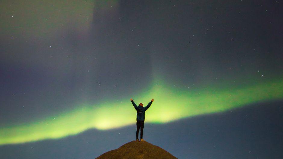 Ein Mann steht auf einem Hügel in Alaska unter grünen Nordlichern.