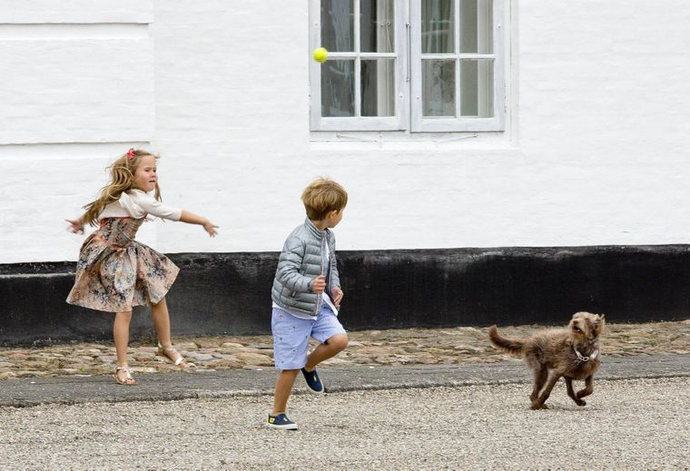 Die Kinder der dänischen Königsfamilie, Prinz Vincent und Prinzessin Josephine, spielen mit einem Hund