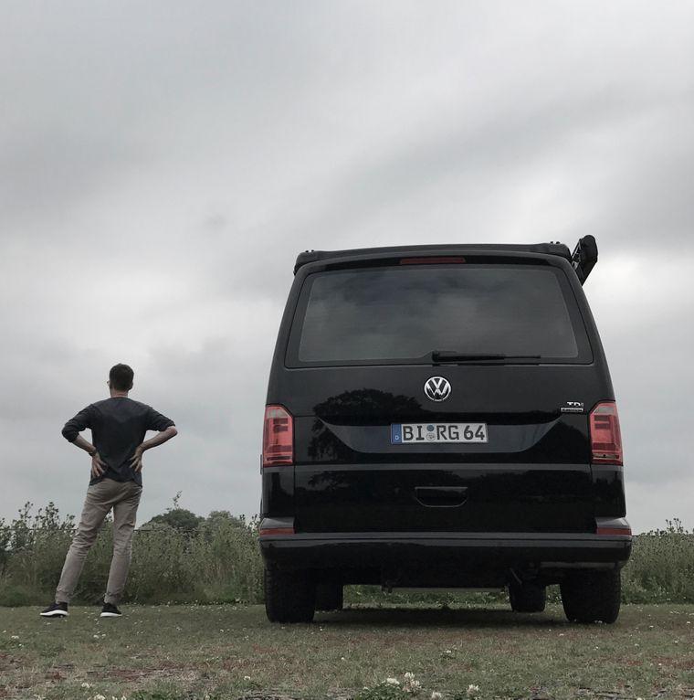 Rolf Grotegut steht neben seinem Bulli, mit dem er einen Roadtrip durch Europa macht.