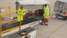 Zwei Gepäckabfertiger am Airport Manchester werfen die Koffer in hohem Bogen in den Wagen.