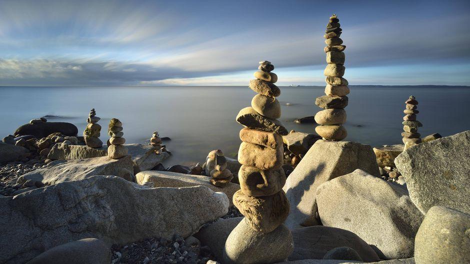 Aufeinandergestapelte Steine an einem Strand.