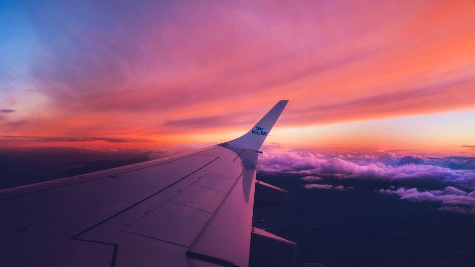 Tragflächen einer KLM-Maschine vor pink Wolken.