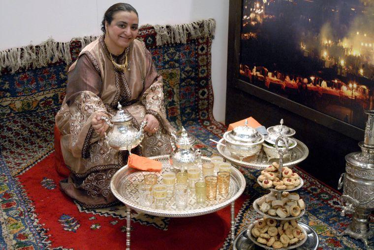 Marokkanerin präsentiert auf traditionelle Weise Pfefferminztee.