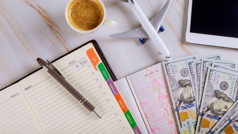 Schreibtisch mit Kalender, Tablet, Mini-Flugzeug und Kaffee.
