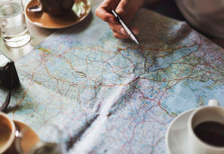 Reiseplanung beim Kaffeetrinken mit Landkarte von Schweden.