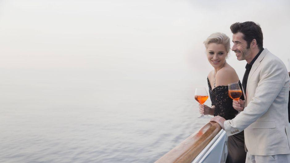 Ein Paar mit Aperitiv steht auf dem Deck eines Kreuzfahrtschiffs.