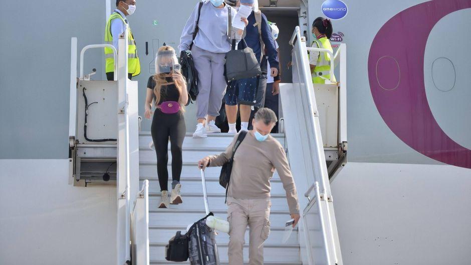 Passagiere mit Mundschutz steigen aus einem Flugzeug. In immer mehr Ländern müssen sich Urlauber vorab registrieren.