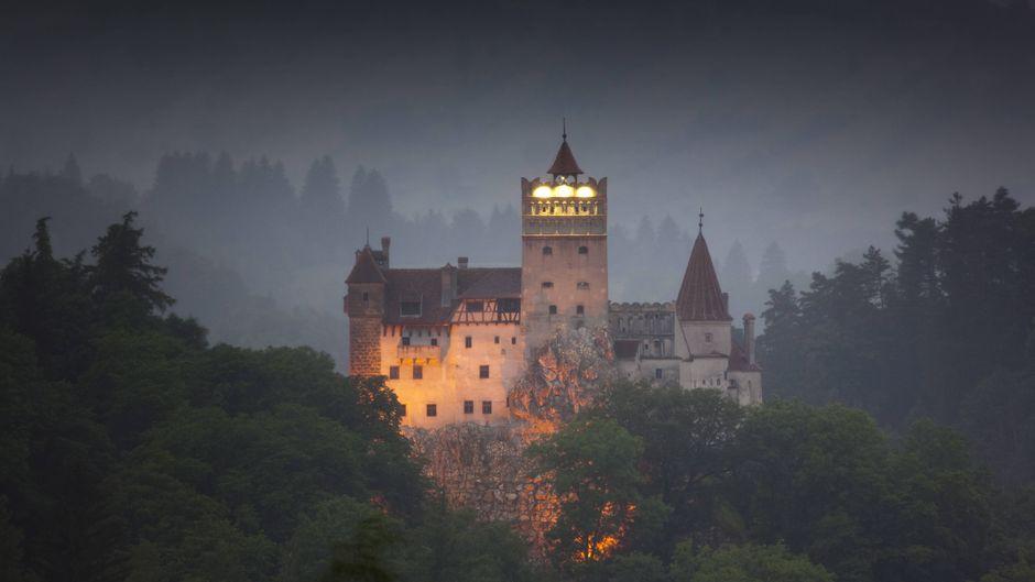Das Draculaschloss in Bran leuchtet in der Abenddämmerung