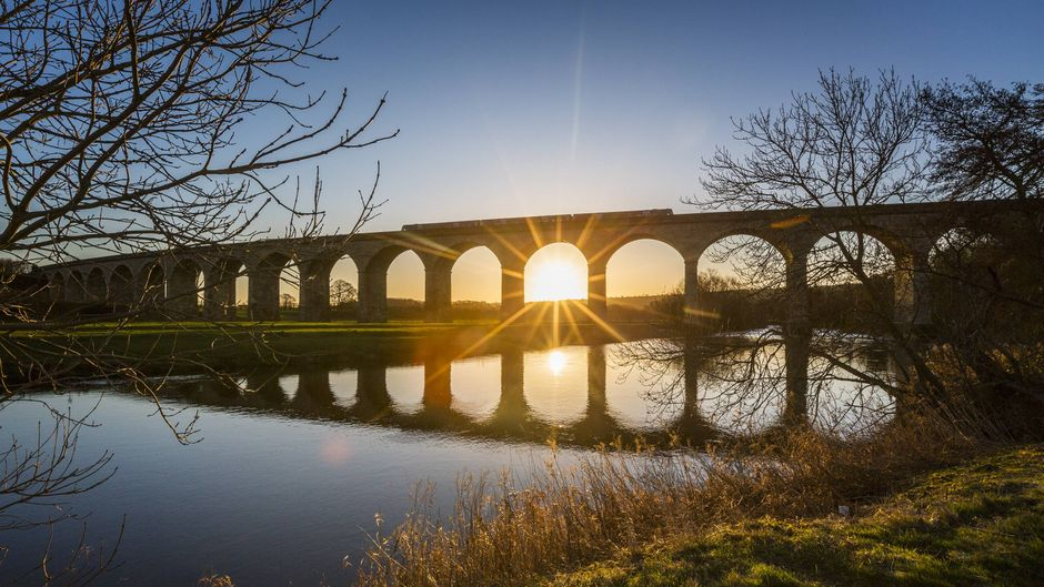 Ein Zug auf einer Brücke bei Sonnenaufgang.