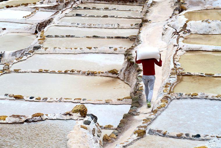 Ein Mann trägt einen Sack Salz durch die Salzpfannen bei Maras.