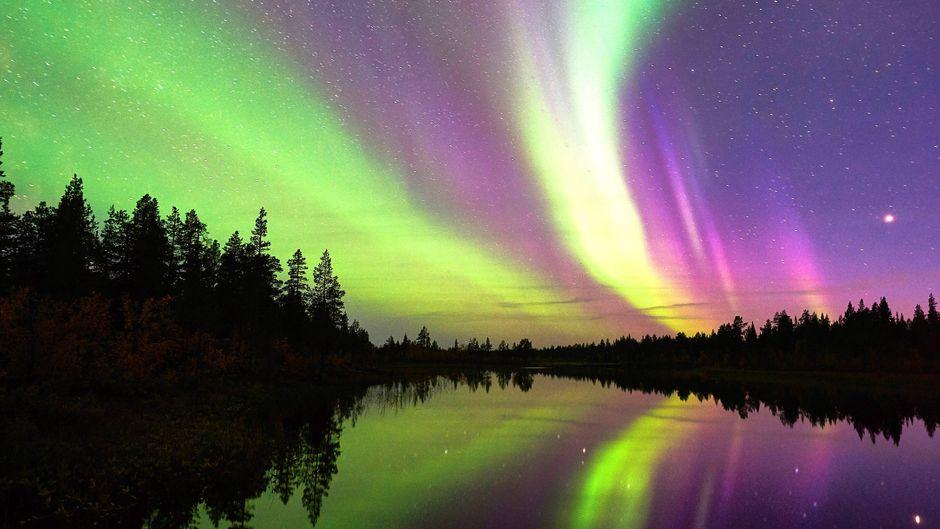 Nordlichter spiegeln sich in einem See im schwedischen Lappland.