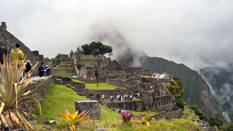 Touristen besuchen Machu Picchu.