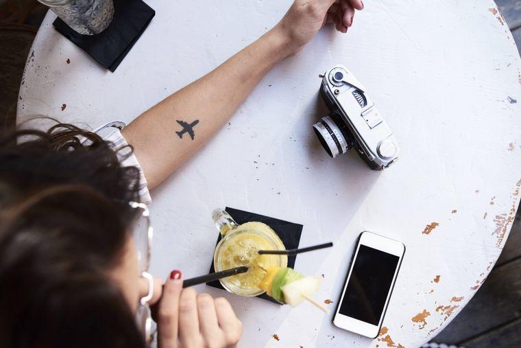 Junge Frau mit Flugzeug-Tattoo trinkt Saft in einem Café.