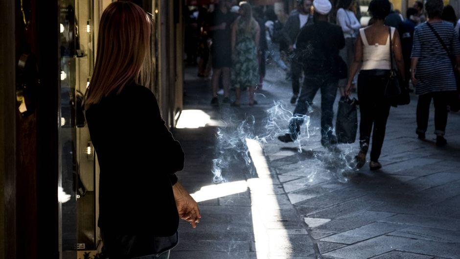 Eine Frau raucht in den Gassen von Venedig.