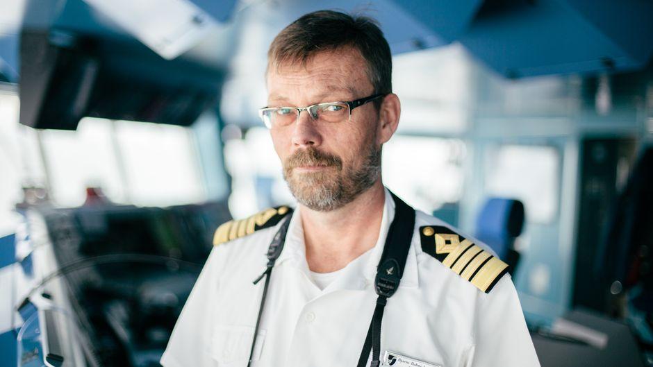Der Kapitän eines Kreuzfahrtschiffes auf der Brücke.