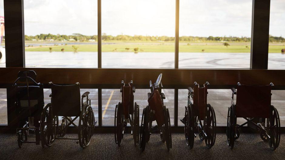 Rollstühle am Fenster in einem Flughafen.