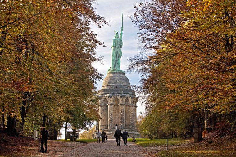 Im Süden des Teutoburger Waldes steht eines der bekanntesten Denkmäler Deutschlands. Zur richtigen Zeit wandern Besucher zwischen gefärbten Bäumen zum Hermannsdenkmal.
