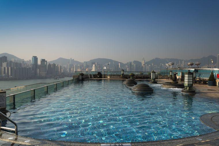 Von dem Pool auf dem Dach des Harbour Grand Hotels aus siehst du im Hintergrund die Skyline Hongkongs.