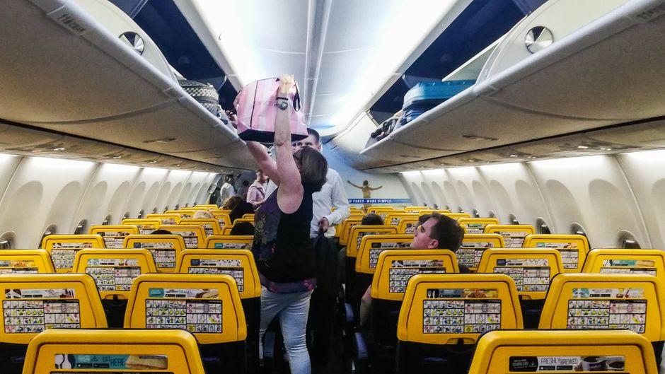 Passagiere verstauen ihr Gepäck im Flieger.