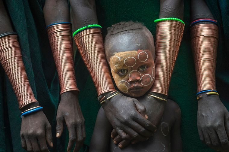 Kleiner Junge zwischen Kupferarmbändern der Suri-Frauen in Äthiopien.
