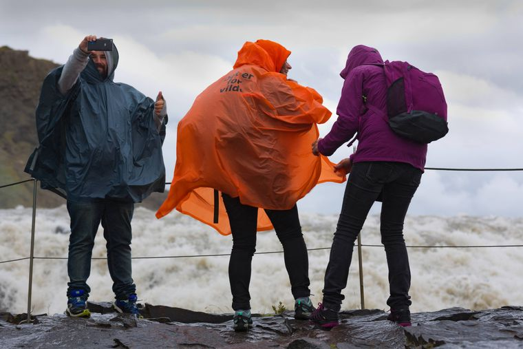 Drei Urlauber machen ein Selfie an der Klippe.