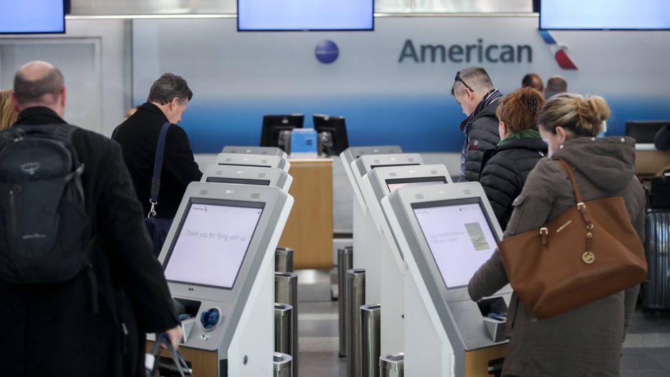 Flugpassagiere beim Self-Check-in.