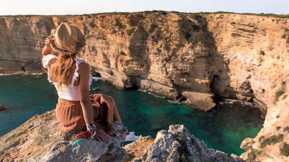 Eine Urlauberin sitzt an der Algarve auf einem Felsen mit Blick aufs Meer.