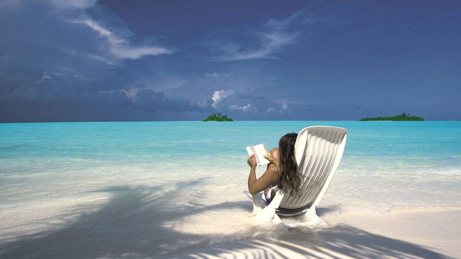Eine Frau liest im Liegestuhl auf einem Maledivenstrand.