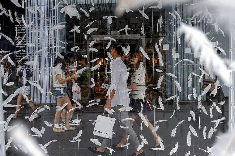 Federn und Fußgänger im Shopping-Trubel.