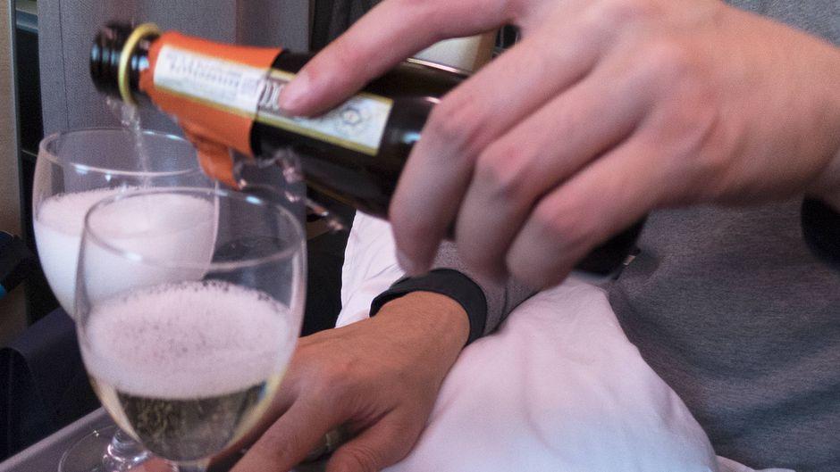 Ein Passagier schenkt sich ein Glas Sekt ein.