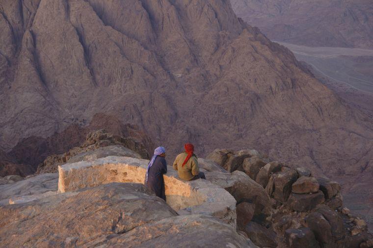 Zwei Pilger schauen vom Berg Sinai ins Tal.