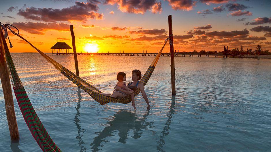 Mutter und Tochter genießen den Sonnenuntergang auf Holbox in Cancún in einer Hängematte im Meer.