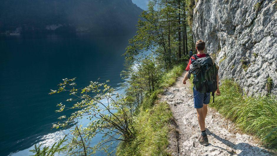Wanderer auf Wanderweg am Ufer des Königssee.