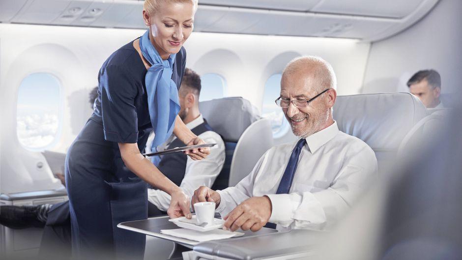 Eine Stewardess bringt eine Tasse Kaffee zum Fluggast.