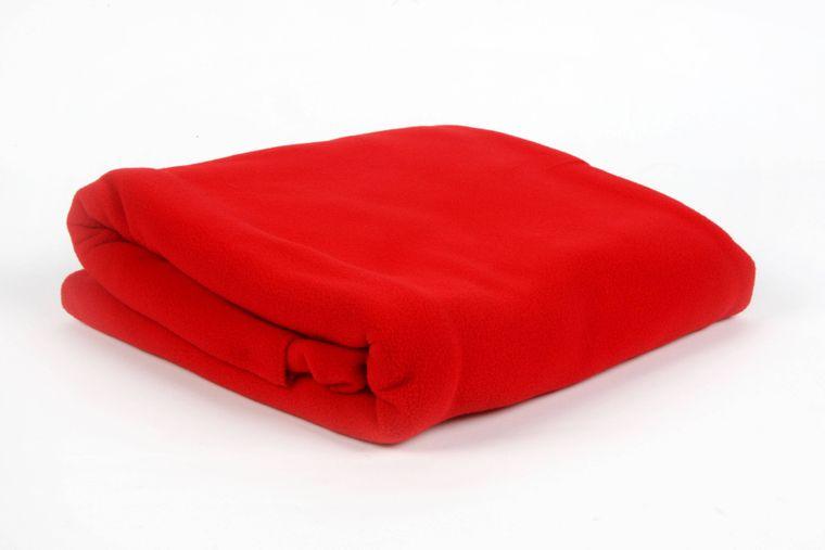 Eine rote Fleecedecke liegt zusammengefaltet auf dem Boden.