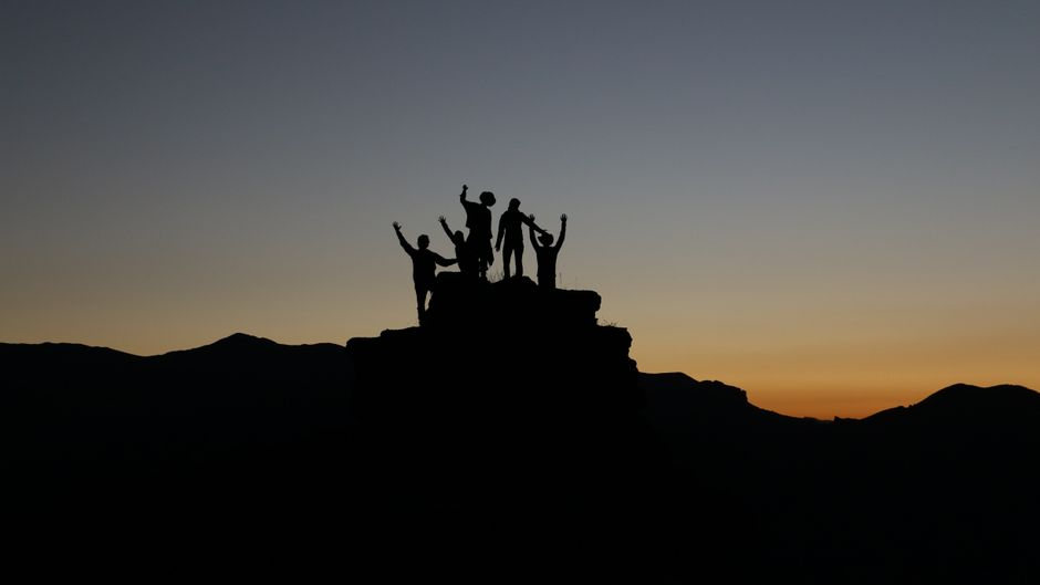 Fünf Menschen stehen auf einem Berggipfel bei Sonnenuntergang.