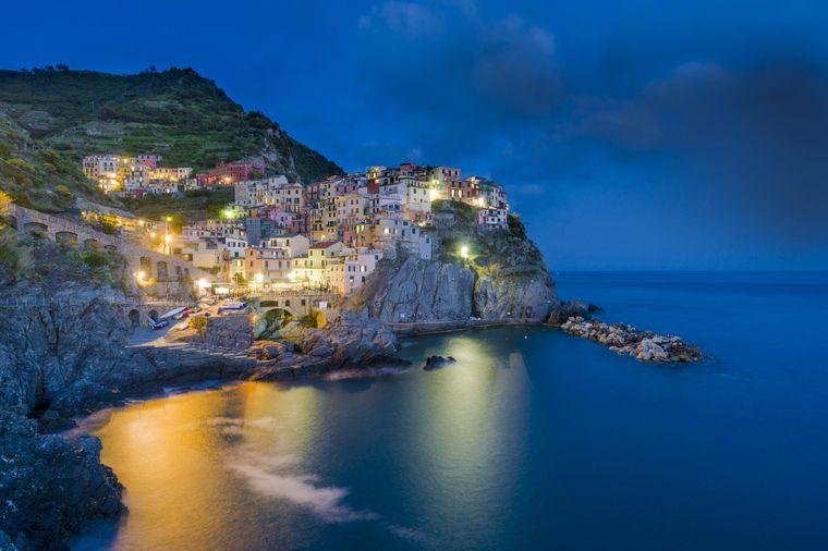 Die beleuchtete Stadt Manarola, Teil der Cinque Terre, in malerischer Lage auf  einem Hügel an der Mittelmeerküste in Italien.