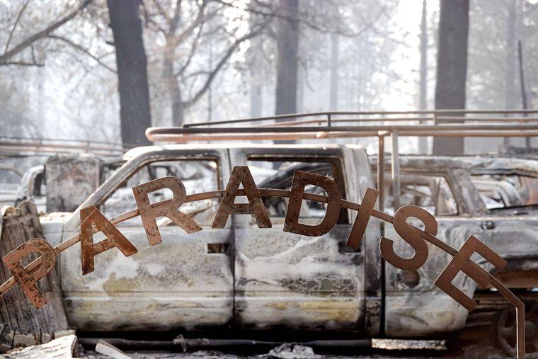 """Schild mit dem Schriftzug """"Paradise"""" vor abgebrannten Autos in Kalifornien."""