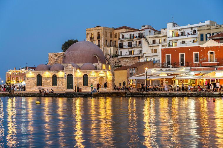 Die Altstadt mit Restaurants und die Hasan-Pascha-Moschee am alten venezianischen Hafen in der Abenddämmerung in Chania.