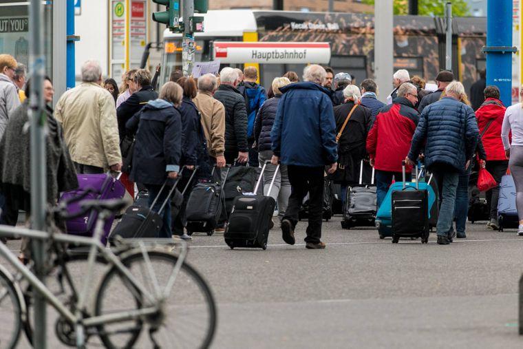 Reisende in Berlin ziehen Rollkoffer hinter sich her.